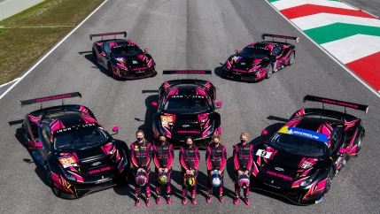 The Iron Dames line up in front of their race cars on the race track.