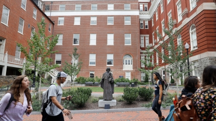 In this Sept. 1, 2016 file photo, a Jesuit statue is seen in front of Freedom Hall, formerly named Mulledy Hall, on the Georgetown University campus in Washington.