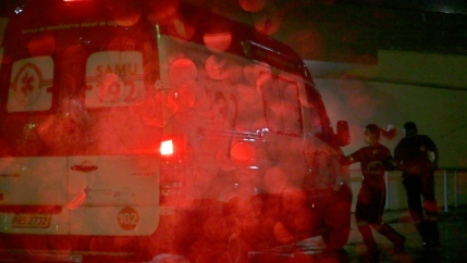 Two people are shown in shadow running toward an ambulance with red brake lights on in the rain.