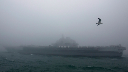 A large military vessel is shown in the distnace amid foggy weather conditions.