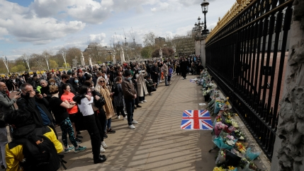 A large crowd of people are shown outside of the tall black iron gates of Buckingham Palace.