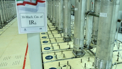 A row of tall stainless steel centrifuges are shown.