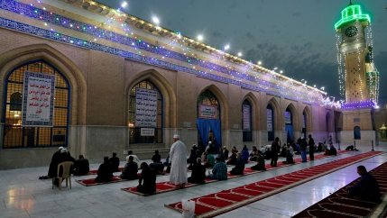 Several rows of people are shown kneeling next to a building with bright lights strung across the top.