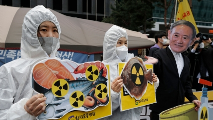 A protester is shown wearing a white radiation protection suit and holding a sign with cuts of fish and the radioactive symbol.