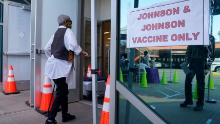 A person is shown wearing a dark vest and white shirt and walking with a cane into a facility with a Johnson & Johnson sign on the outside.