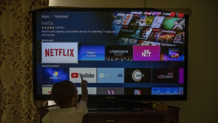 A child looks up at a TV screen with several apps to choose from at his home in New Delhi, India.