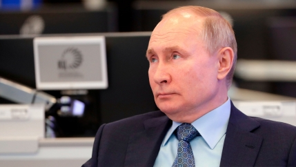 Russian President Vladimir Putin is shown in a close-up photograph wearing a dark suit and tie and looking off to his right.