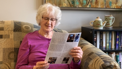A 91-year-old white woman with gray hair, wearing glasses and a pink top, sits on a sofa and reads a newsletter.