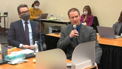 Derek Chauvin in gray suit hold microphone as he speaks, while sitting next to his lawyer
