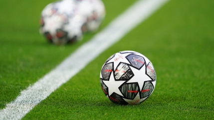 A soccer ball with stars on it rests on a green field near a white line and a soccer ball on the other side.
