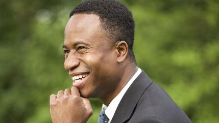 African American Mayor Mike Elliott poses in a dark gray suit