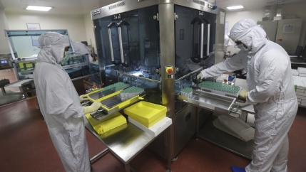 Two lab technicians dressed in white protective gear organize vials.