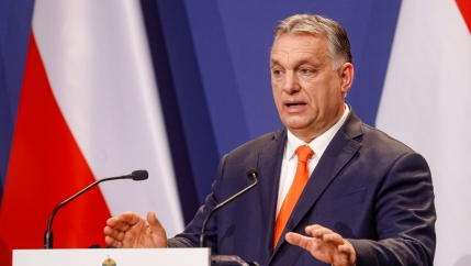Hungarian Prime Minister Viktor Orban is shown wearing a blue suit and orange tie while speaking at a podium with two microphones.