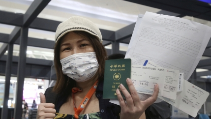 A Taiwanese woman wearing a mask and a white hat holds her passport and airline tickets before she boards a plane.