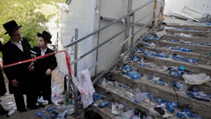 Two young Jewish men are shown wearing Ultra Orthodox clothing and looking on to a staircase strewn with debris following a stampede.