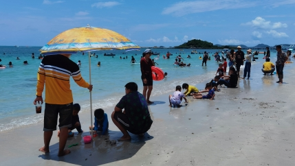 People spend the first day of the Songkran New Year holidays at Nang Rong beach in Chonburi, Thailand, April 13, 2021.