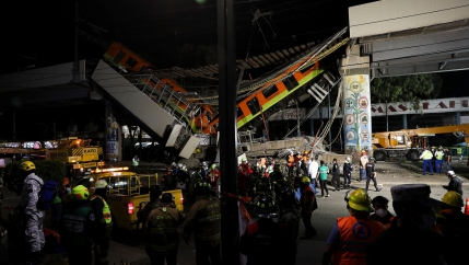 Two subway cars are show fallen from an elevated train track with rescue workers all around.