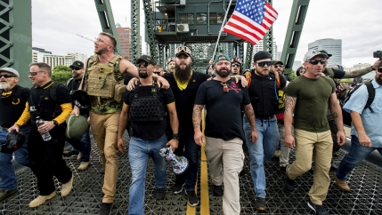 A group of men, mostly white, march with a US flag along a bridge.