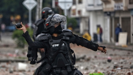 A police officer is shown wearing all black riot gear and face shield while throwing a stun grenade.