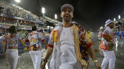 Comedian and actor Paulo Gustavo is shown wearing mostly white and brightly colored overshirt and smiling among other Carnival goers.