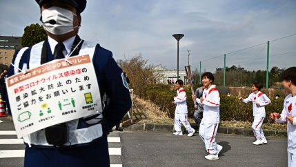 A security official is shown in the nearground with a sign listing COVID-19 safety precautions with several people in roadway behind him and one woman carrying the golden Olympic torch.