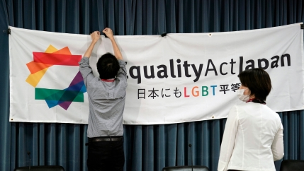 A person is shown clipping a large banner with the words,