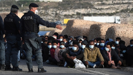 Migrants wearing face masks to curb the spread of COVID-19 sit at a pier as Italian police officers stand by.
