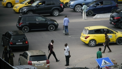 Pedestrians cross a busy street in Kinshasa.