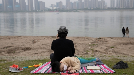 A young child is shown laying on a striped blanket and wearing a mask with a man sitting and facing the opposite direction looks on at the Yangtze River.