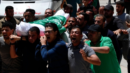 A group of people are shown carrying a body draped in white and the green flag of Hamas.