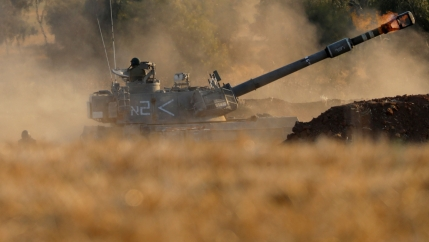 A tank is shown in the distance with a soldier on top and fire coming out of the barrel.