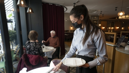 A waiter wearing a mask and an apron with her hair pulled back tends to a dining table.