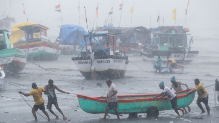 A group of people are shown amid heavy rainfall pushing and pulling a teal blue boat on two wheels.