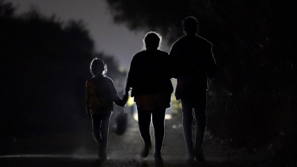 Figures of a 7-year-old migrant girl walking with a woman and unidentified man silhouetted at night