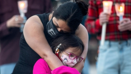 A woman is shown wearing a dark shirt and face mask while hugging a young girl who is wearing a pink shirt.