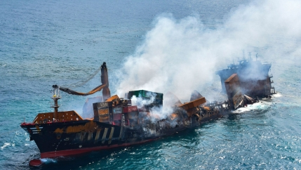 A large cargo ship is shown smoking and sinking into the ocean.