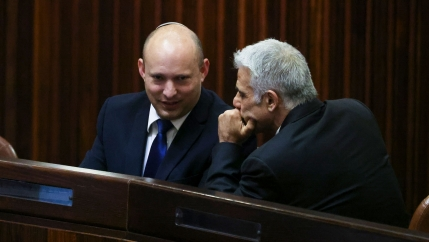 Yamina party leader Naftali Bennett wearing a dark suit and sitting while speaking with Yesh Atid party leader Yair Lapid on his left.