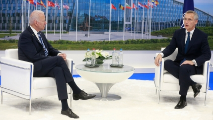 NATO Secretary General Jens Stoltenberg and US President Joe Biden are shown both wearing suits and sitting in white armchairs.