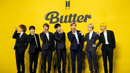 Seven members of K-pop band BTS stand wearing black suits in front of a yellow background that says