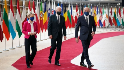 Joe Biden, Charles Michel and Ursula von der Leyen are shown walking side-by-side on a red carpet with several national flags in the background.