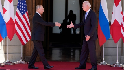 President Joe Biden and Russian President Vladimir Putin are shown walking toward each other with their hands outstretched for a shake.