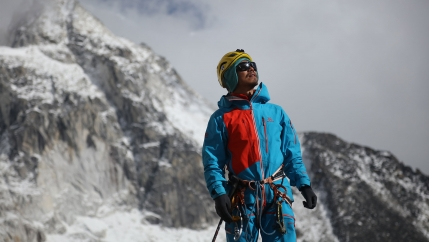Man wearing a blue coat and sunglasses holds his head up to the sun with a snowy mountain in the background