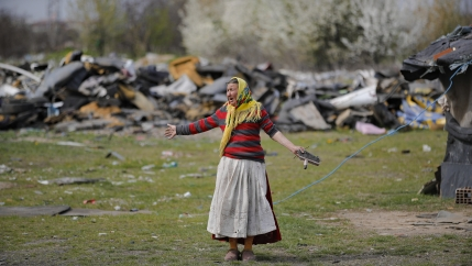 A Roma woman wearing red, white, and yellow stands in shock with her arms spread out during a raid