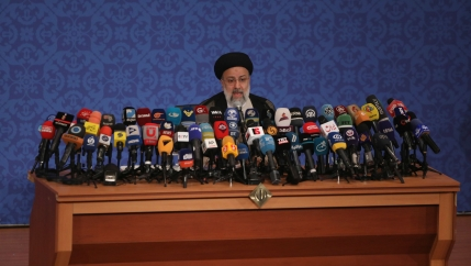 Iran's new President-elect Ebrahim Raisi is shown standing at a podium with several dozen microphones.