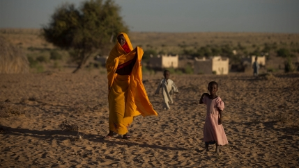 Woman in orange outfit walks in dry climate with girl in pink dress and boy in beige outfit