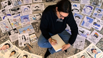 A man is shown sitting cross-legged with dozens of cartoons on the floor all around him.
