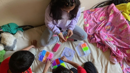 Dinora Hernandez's three children make bracelets at home in Oakland, California. Every Tuesday, Hernandez heads to a local food bank, assistance that allows her to wire cash to family in El Salvador.