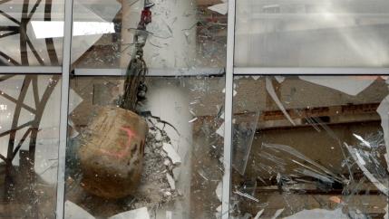 Wrecking ball smashing through glass window