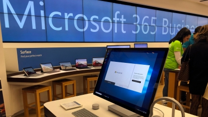 A computer monitor is shown in the nearground with a row of tablet computers in the distance under a Microsoft banner.