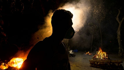 A man is shown in shadow wearing a face mask with several large glowing orange funeral pyres in the distance.